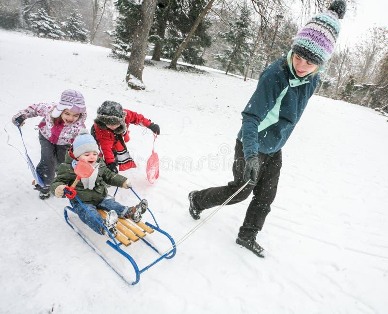 A mãe caçoa o trenó do divertimento da neve imagens de stock royalty free