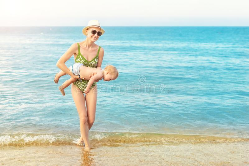Mãe calva bonita nova que leva a água azul clara caucasiano bonito do menino da criança para fora na praia tropical com chuva mor foto de stock