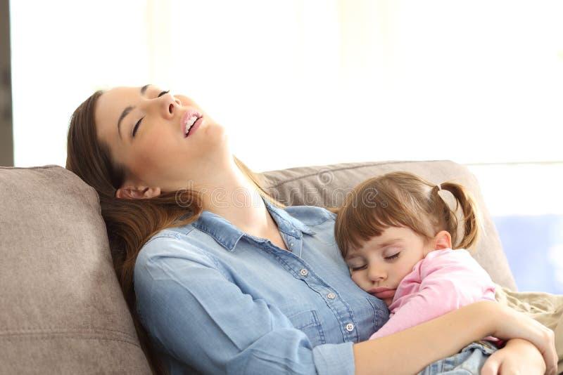 Mãe cansado que dorme com sua filha do bebê