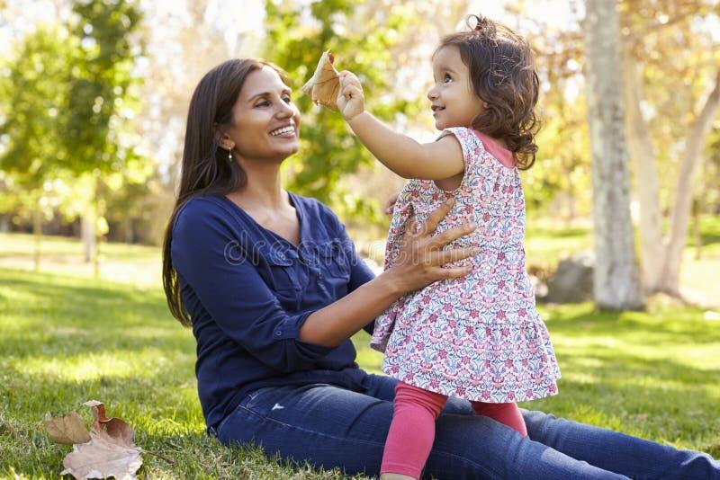 Mãe caucasiano asiática da raça misturada e filha nova no parque imagens de stock