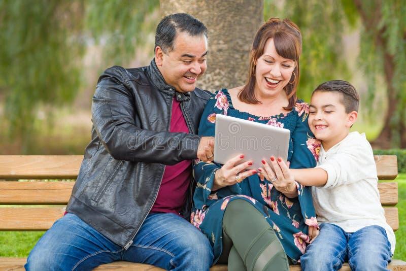 Mãe caucasiano entusiasmado e pai latino-americano Using Computer Tablet com ar livre do filho da raça misturada foto de stock royalty free