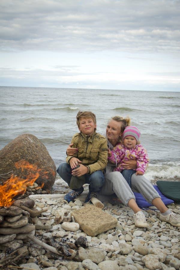 Mãe com as crianças no mar na queda imagem de stock