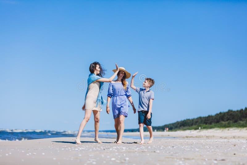 Mãe com as crianças que andam pelo mar imagens de stock royalty free