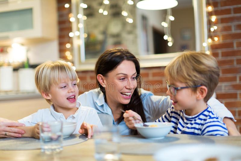 Mãe com as crianças que comem o café da manhã imagem de stock