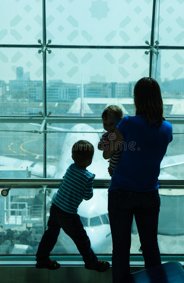 Mãe com as crianças que esperam no aeroporto imagem de stock royalty free