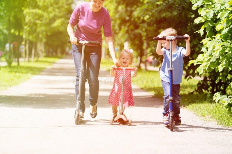 Mãe com as crianças que montam o 'trotinette' no verão imagens de stock