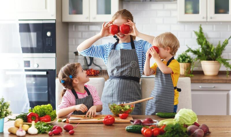 Mãe com as crianças que preparam a salada vegetal fotos de stock royalty free
