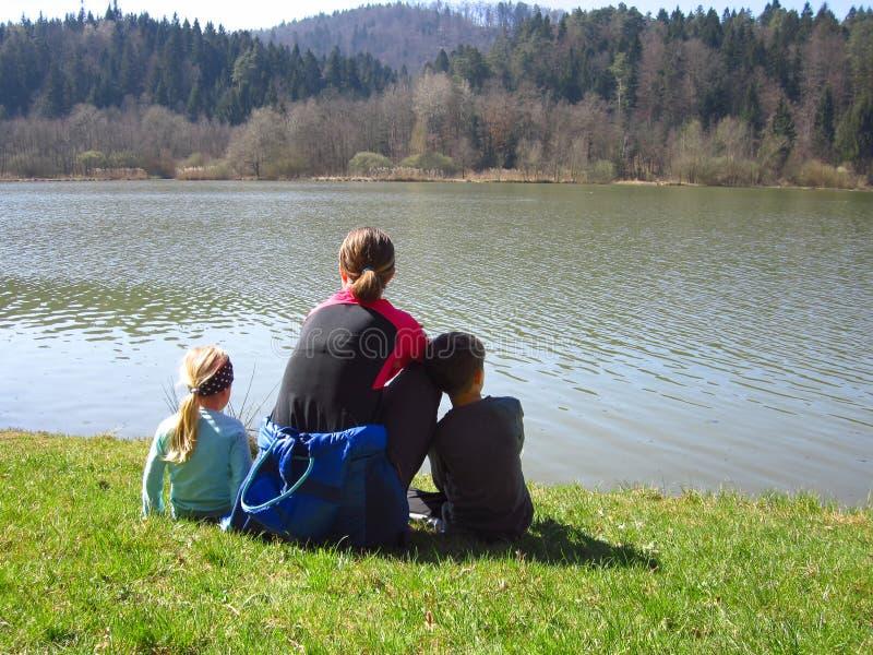 Mãe com as crianças que sentam-se pelo lago imagens de stock royalty free