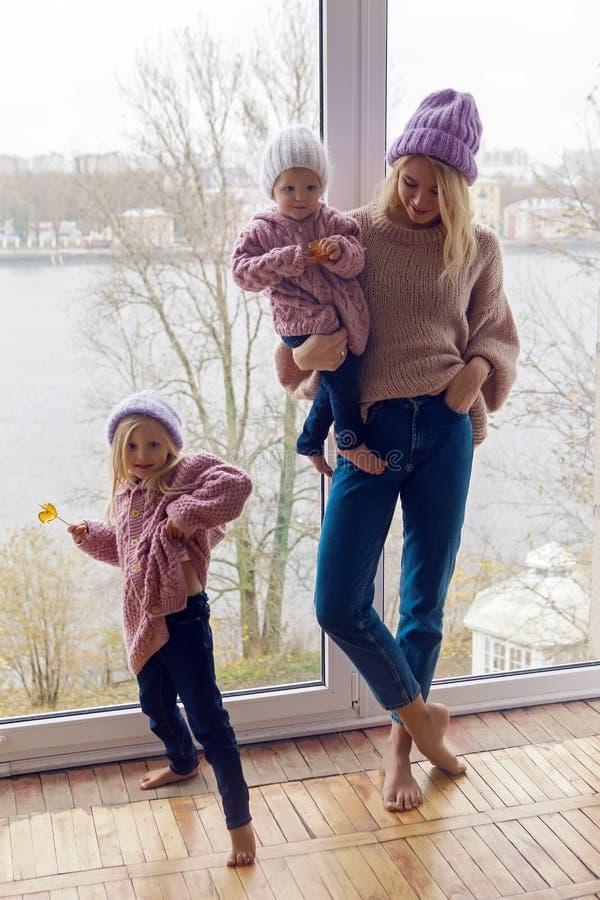 Mãe com as duas filhas em estar morno da roupa foto de stock royalty free