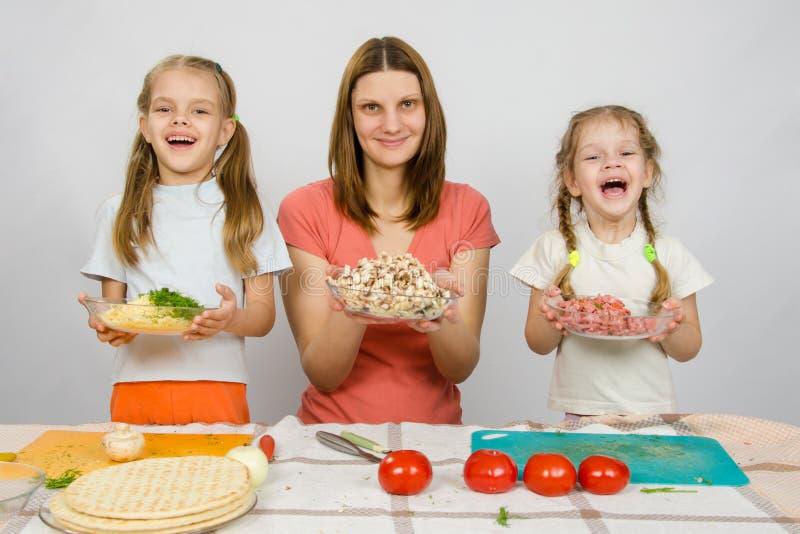 Mãe com as duas filhas que guardam felizmente a placa com os produtos cortados para a pizza foto de stock royalty free