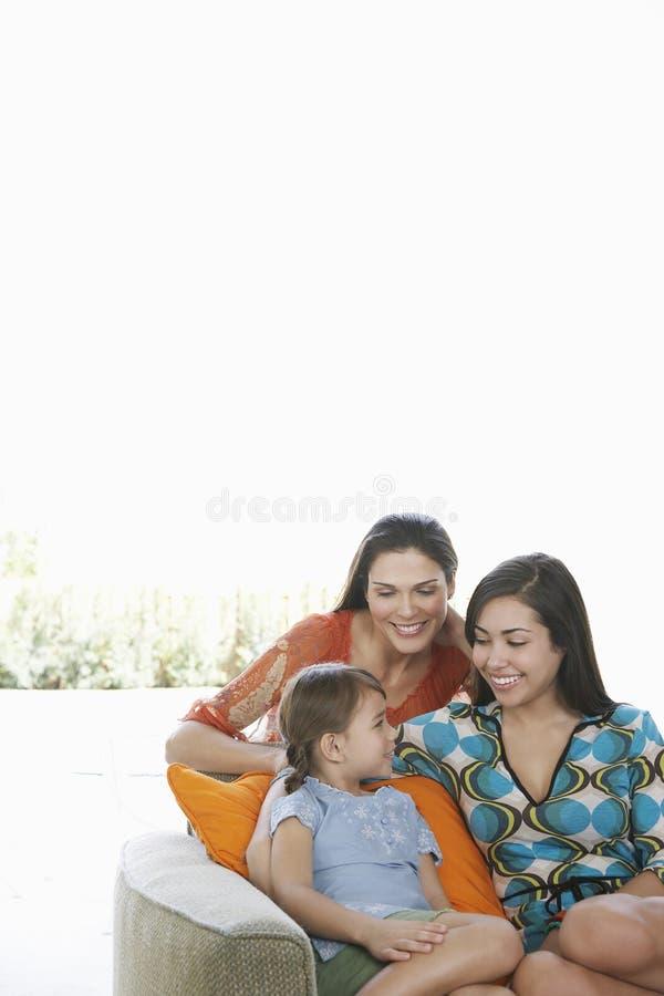 Mãe com as filhas que relaxam no sofá foto de stock royalty free
