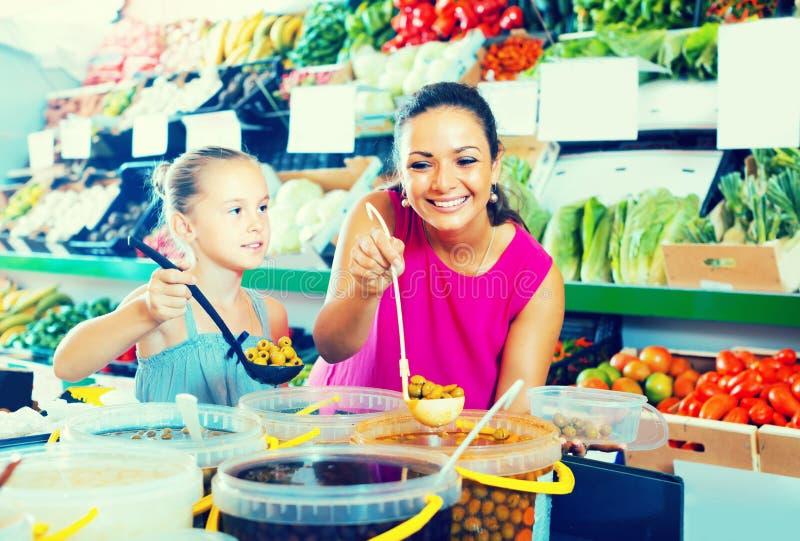 Mãe com azeitonas da colheita da menina na loja de alimento foto de stock royalty free