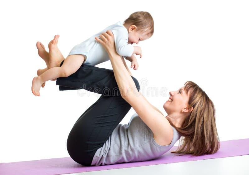 A mãe com bebê faz exercícios ginásticos imagens de stock