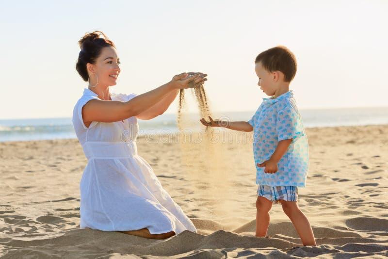 Mãe com brincadeira com a areia na praia do mar fotos de stock royalty free