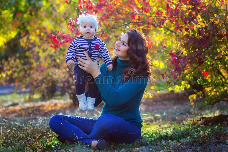 A mãe com a criança no parque senta-se sob uma árvore fotografia de stock royalty free