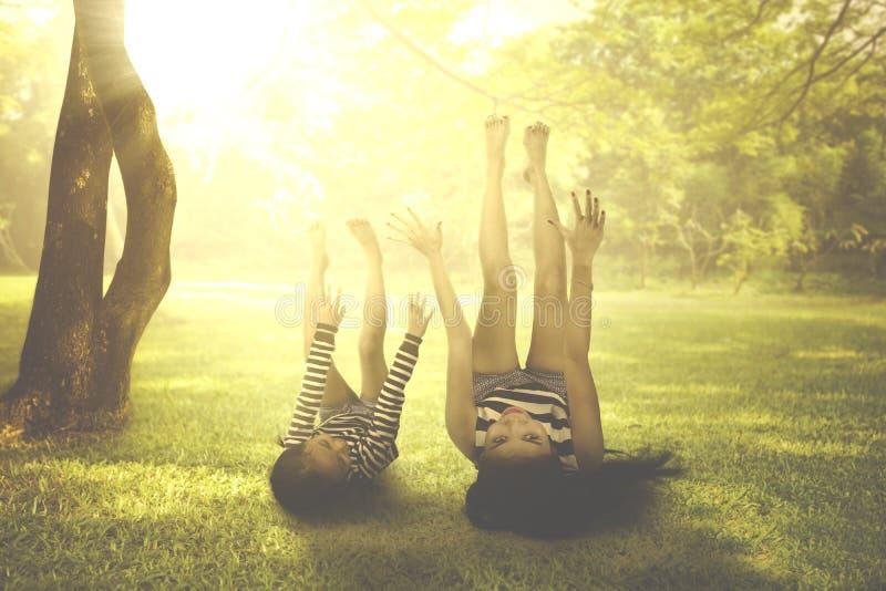 Mãe com a criança que encontra-se para baixo sob a luz solar fotos de stock