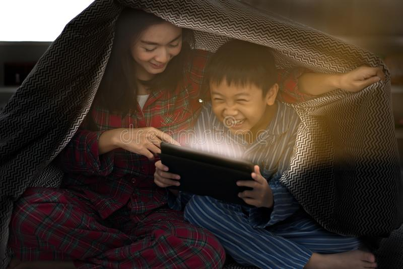 Mãe com a criança que usa a tabuleta junto felizmente sob a cobertura fotografia de stock