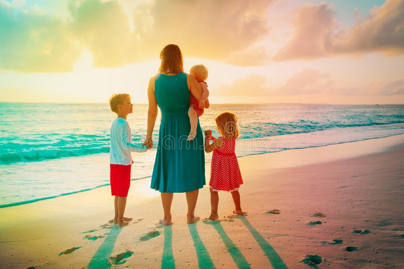 Mãe com crianças olhando o pôr do sol na praia imagem de stock royalty free