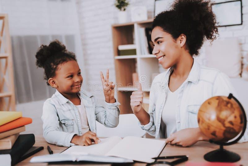 Mãe com DAugter e lições Menina do sorriso fotografia de stock