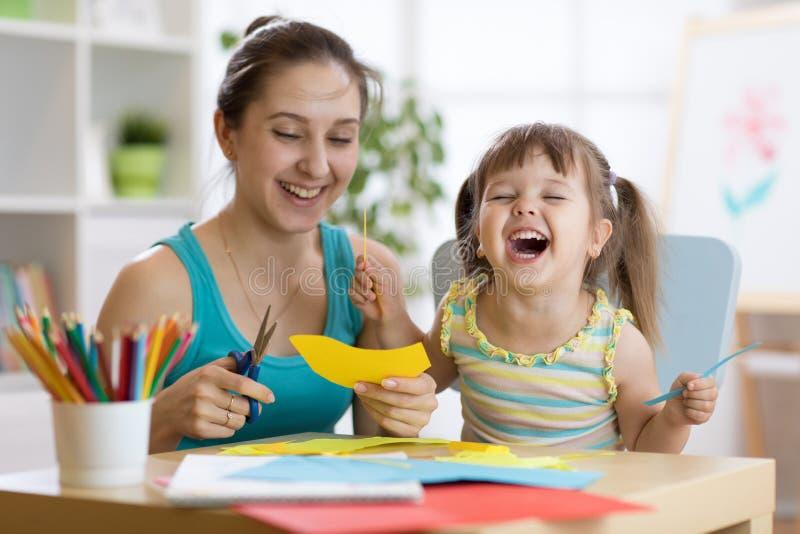 A mãe com divertimento pequeno da filha cortou o papel colorido das tesouras fotografia de stock royalty free