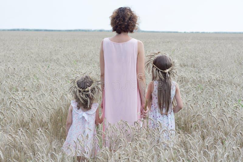 A mãe com estada de duas filhas no campo de trigo para trás vê Apreciando a natureza fotografia de stock royalty free