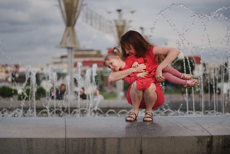 Mãe com a filha bonito na fonte imagem de stock