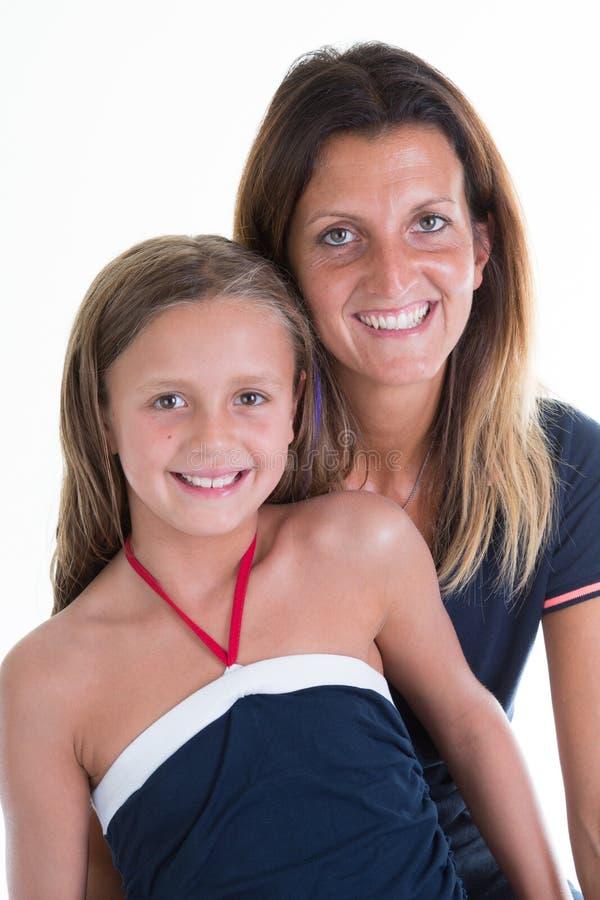 mãe com a filha da criança da beleza que levanta na parede branca imagens de stock royalty free