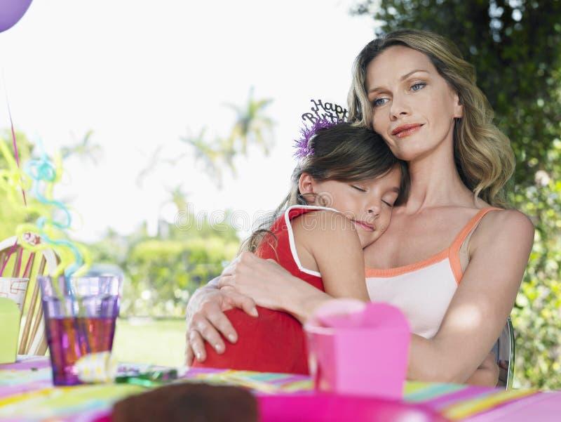 Mãe com a filha de sono na tabela do aniversário fotos de stock royalty free