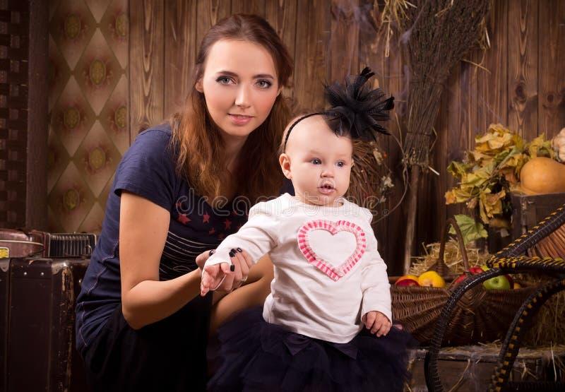 Mãe com a filha do bebê no partido de Dia das Bruxas imagem de stock