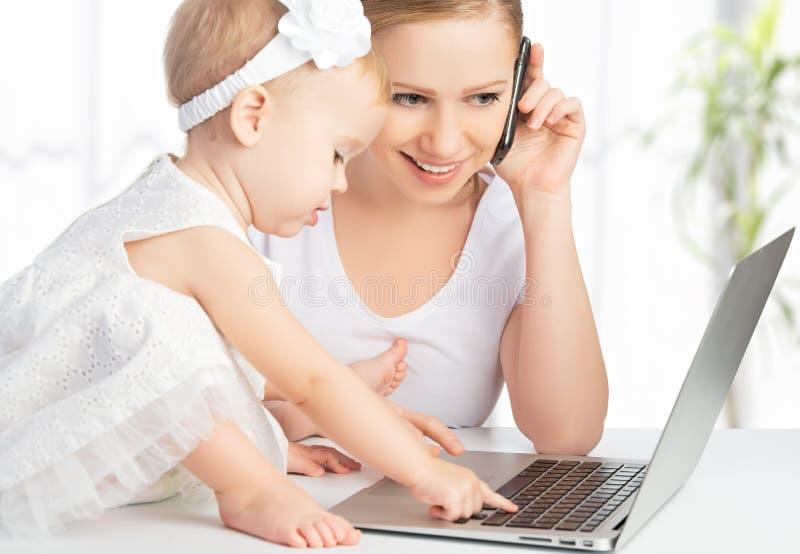 A mãe com filha do bebê trabalha com um computador e um telefone fotos de stock