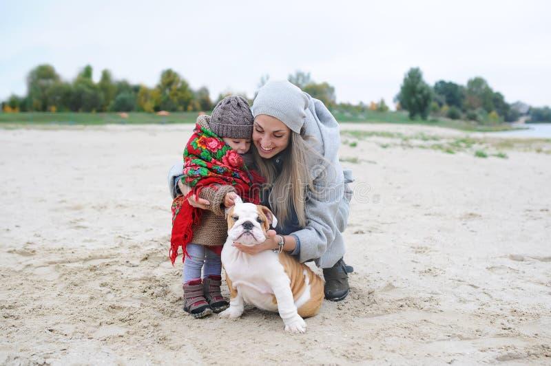 Mãe com a filha e o cachorrinho pequenos de um buldogue no outono fora imagem de stock