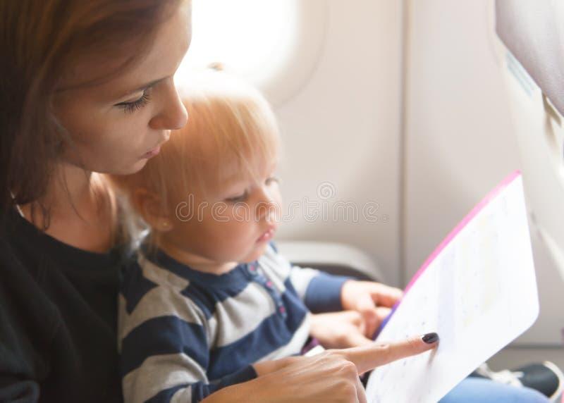A mãe com filha leu uma segurança a bordo imagem de stock