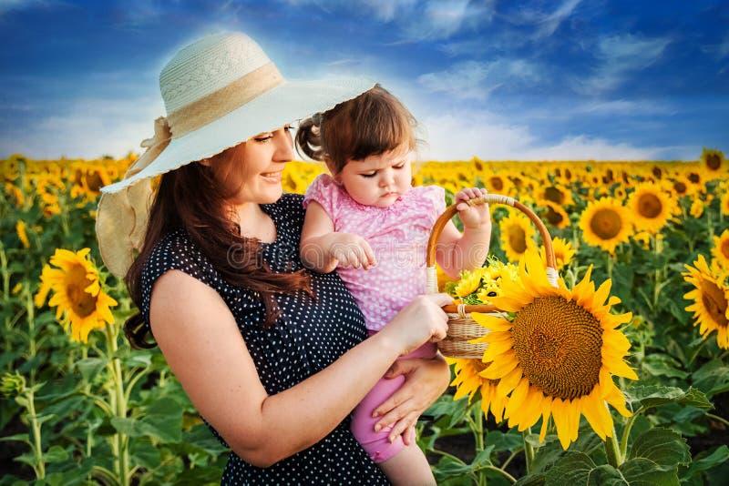 Mãe com a filha no campo com girassóis foto de stock