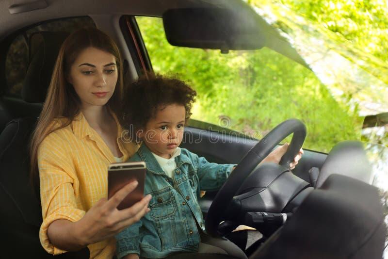 Mãe com a filha pequena que conduz o carro e que conversa no telefone fotografia de stock royalty free