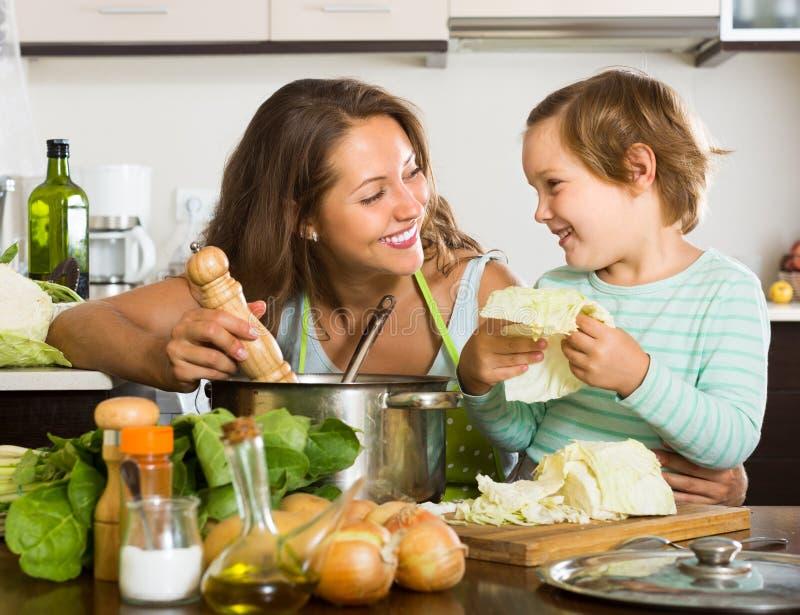 Mãe com a filha pequena que cozinha em casa fotografia de stock royalty free