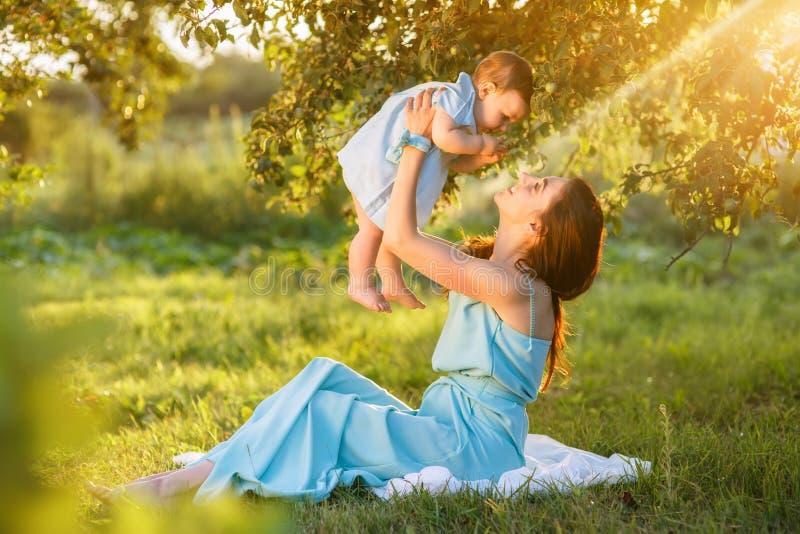 Mãe com a filha pequena que joga na grama verde fotografia de stock royalty free