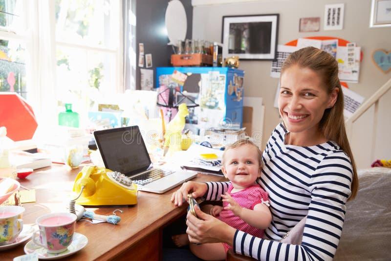 Mãe com a filha que corre a empresa de pequeno porte do escritório domiciliário imagem de stock