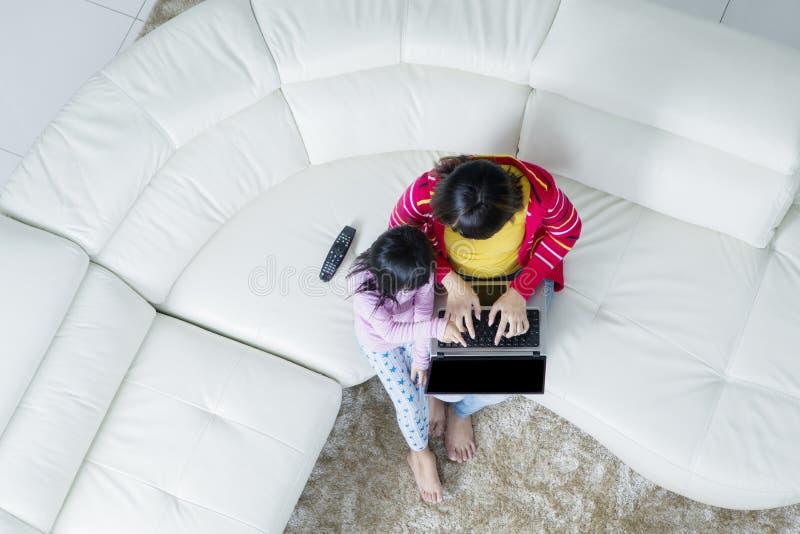 Mãe com a filha que usa um portátil foto de stock royalty free