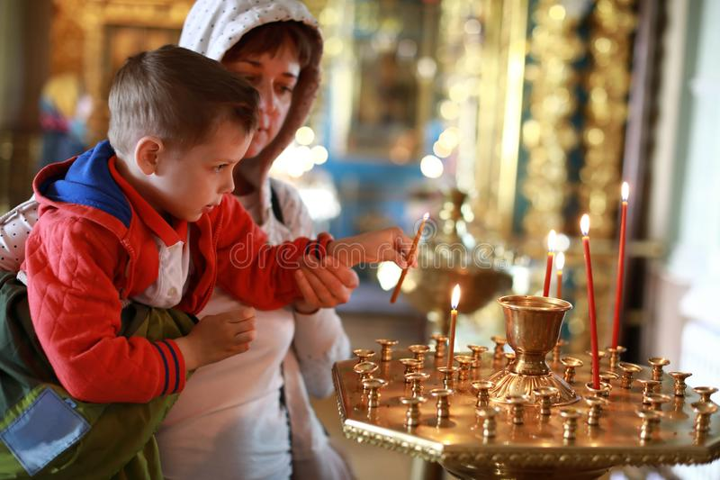 A mãe com filho pôs velas na igreja fotos de stock