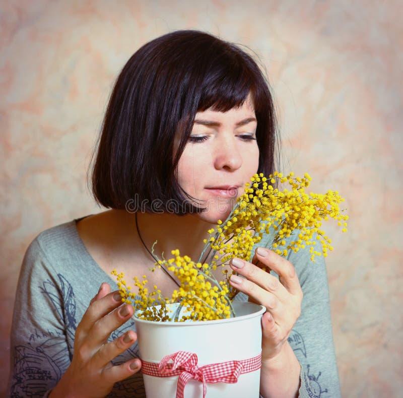 A mãe com flores da mimosa apresentou no dia da mulher foto de stock
