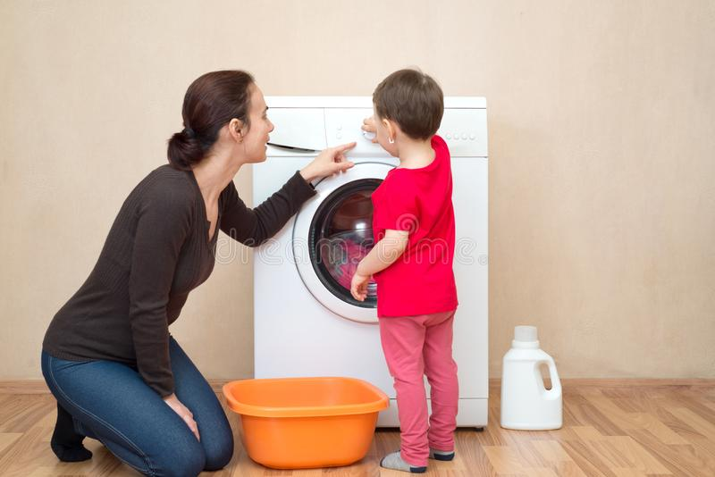 Mãe com a menina perto da máquina de lavar imagem de stock