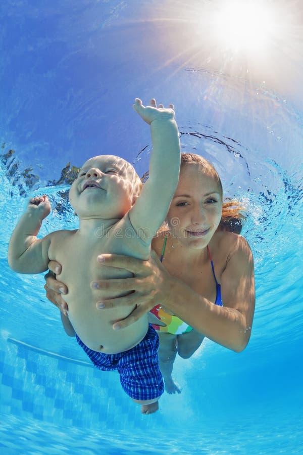 Mãe com a natação e o mergulho da criança subaquáticos na associação imagem de stock royalty free