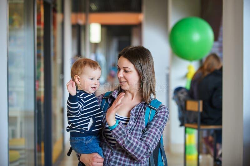 Mãe com o bebê dos anos de idade an1 que anda no shopping A m?e guarda o beb? em seus bra?os fotografia de stock