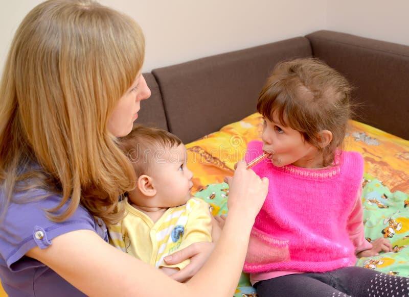 A mãe com o bebê nas mãos dá à medicina doente da menina por meio do batcher tratamento imagens de stock