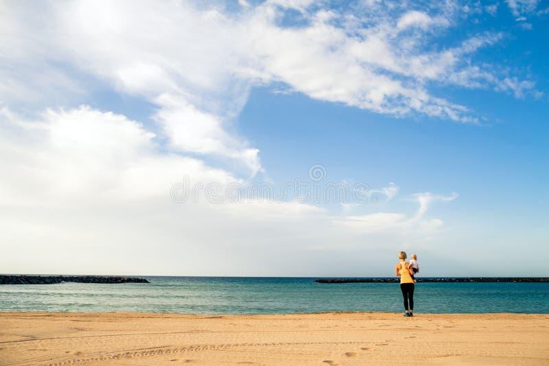 Mãe com o bebê que aprecia o nascer do sol em uma praia fotos de stock