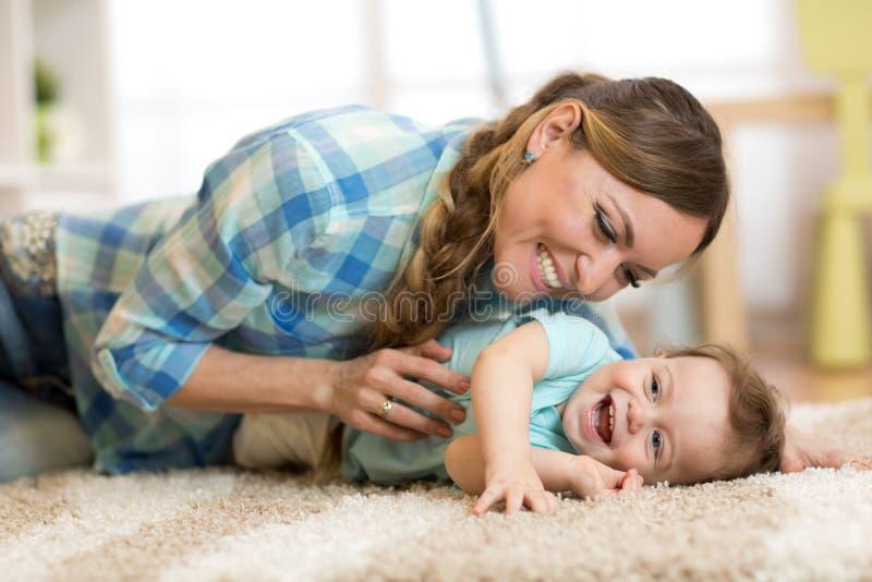 Mãe com o bebê que tem um divertimento em casa fotografia de stock royalty free