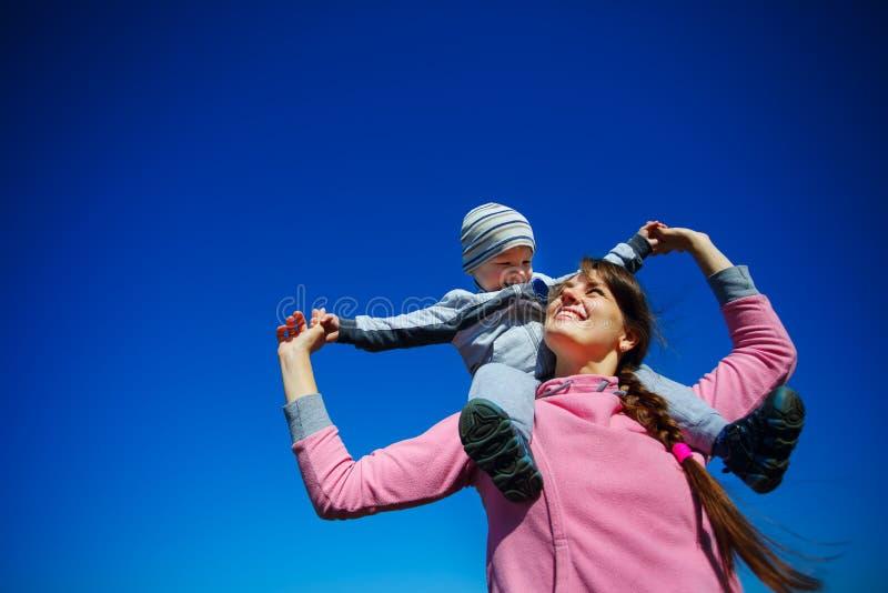 Mãe com o filho contra o céu azul fotos de stock royalty free