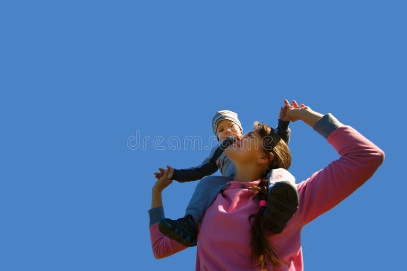 Mãe com o filho contra o céu azul imagens de stock royalty free