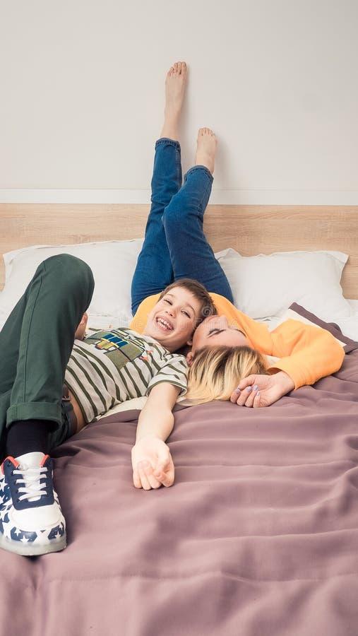 Mãe com o filho na cama, mãe e filho que têm o divertimento foto de stock royalty free