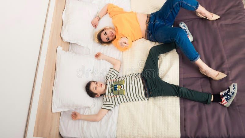 Mãe com o filho na cama, mãe e filho que têm o divertimento fotos de stock royalty free